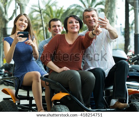Portrait of two couples driving grand tour electric outside and making photos - stock photo