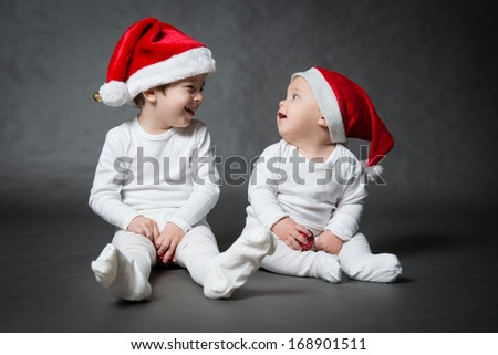 Portrait of two cute boys in Santa hat, gray background - stock photo