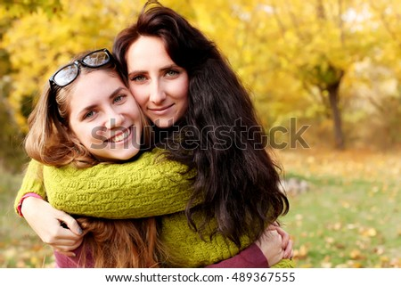 Portrait of two cute girls sisters hugs in autumn park.