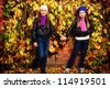 Portrait of two cute girls sisters posing at the autumn park. - stock photo