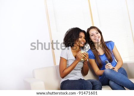 Portrait of two cute girls watching TV on a sofa.