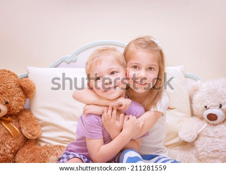 Portrait of two cute kids having fun at home, brother and sister playing in bedroom, healthy lifestyle, family love concept