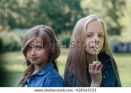 Portrait of two cute little girls enjoying summer outdoors. - stock photo