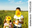 Portrait of two cute little girls hiding behind sunflowers on sunny day - stock photo