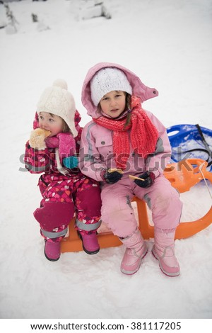 portrait of two cute little girls sitting together on sledges outdoors at snowy winter day, eating tasty cookies on break