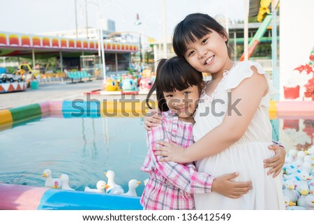 Portrait of two cuties hugging by the pool full of rubber ducks - stock photo
