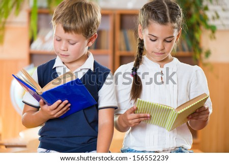 Portrait of two diligent pupil with books in library - stock photo