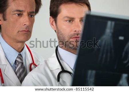 portrait of two doctors examining X-rays - stock photo