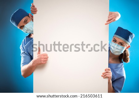 Portrait of two doctors wearing blue medical uniform and masks looking out of the huge poster for copy place. Isolated on blue background - stock photo