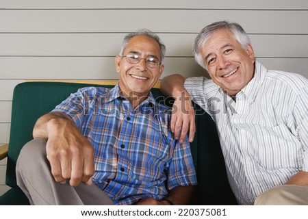 Portrait of two elderly men sitting and smiling - stock photo