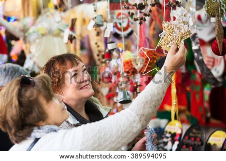 Portrait of two elderly women choosing decorations at counter of Christmas market - stock photo