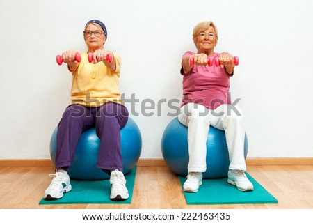 Portrait of Two elderly women doing muscle exercises with weights in gym.
