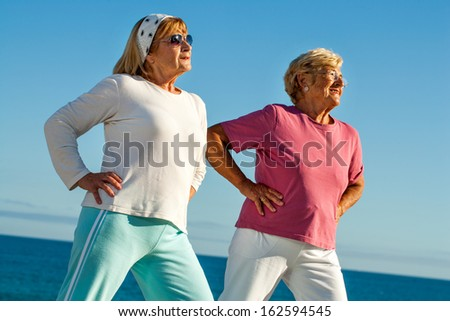 Portrait of two elderly women stretching together outdoors. - stock photo