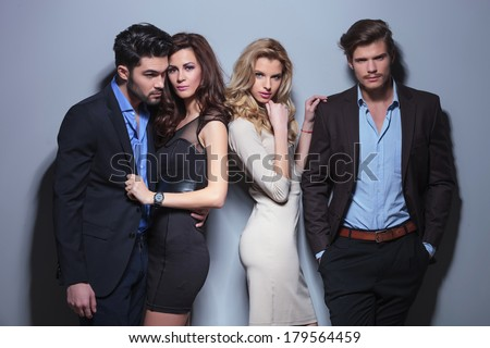 portrait of two elegant women looking into the camera with their men beside them. on a gray background - stock photo