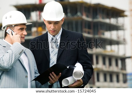 Portrait of two engineers interacting at building site outdoor - stock photo