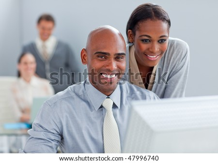 Portrait of two ethnic colleagues working at a computer in the office