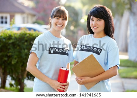 Portrait Of Two Female Charity Volunteers On Street