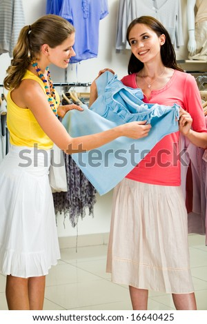 Portrait of two female friends discussing a blue t-shirt - stock photo