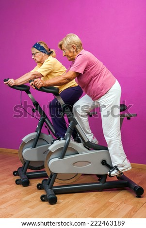 Portrait of Two female seniors at intense spinning session in gym.