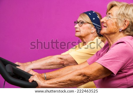 Portrait of two fit Senior women working out on bicycles in health club.