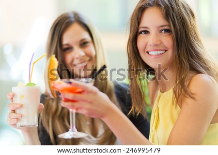 Portrait of two friends drinking a cocktail - stock photo