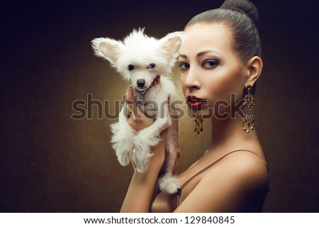 Portrait of two friends:  fashionable model with sexy red lips holding her white little chinese crested dog. Both posing over golden background. Copy-space. Studio shot - stock photo