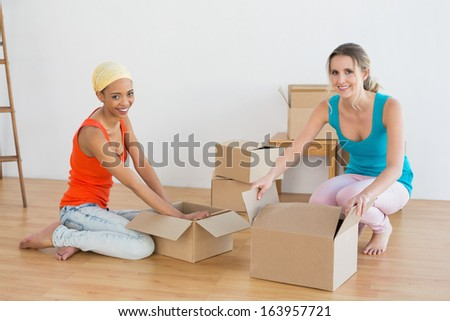 Portrait of two friends moving together in a new house and unwrapping boxes - stock photo