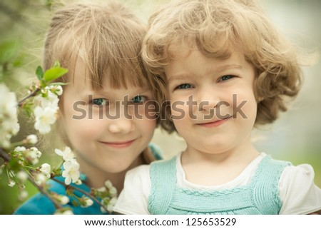 Portrait of two friends with cherry flower in spring park