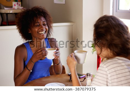 Portrait of two girl friends enjoying a cup of coffee at cafe - stock photo
