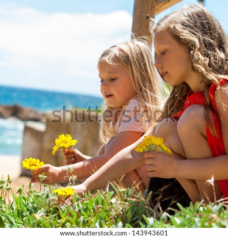 Portrait of two girlfriends picking flowers at seaside. - stock photo