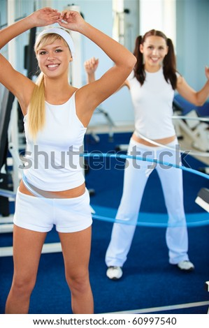 portrait of two girls exercising with hula hoops in gym - stock photo