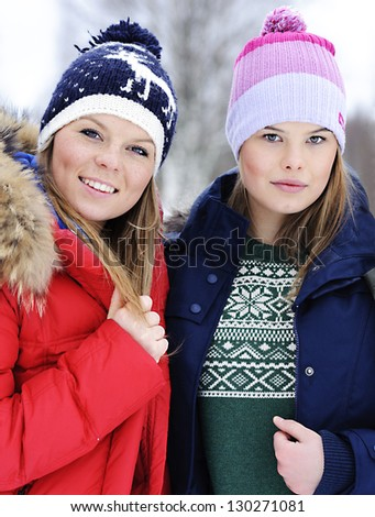 Portrait of two girls in caps on the street in winter