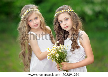 Portrait of two girls in the woods girlfriends - stock photo