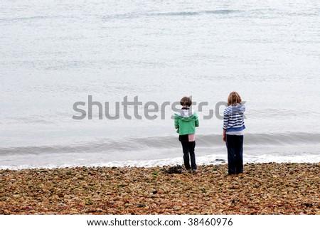 portrait of two girls on pebble beach - stock photo