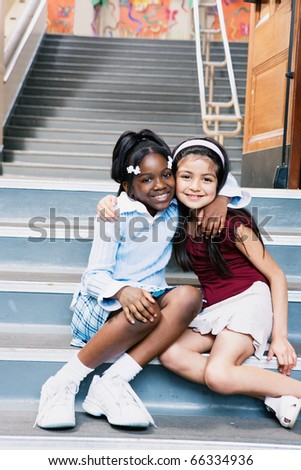 Portrait of two girls sitting on school stairs - stock photo