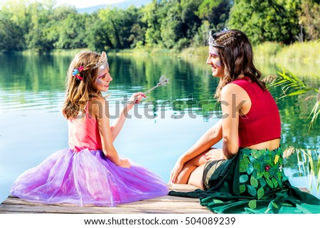 Portrait of two girls sitting on wooden deck next to lake.Girls dressed up in fantasy dresses and make up.