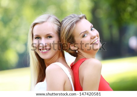 Portrait of two girls who are having pretty much fun in the park. They are talking, discussing, laughing at each other and have a really good time - stock photo