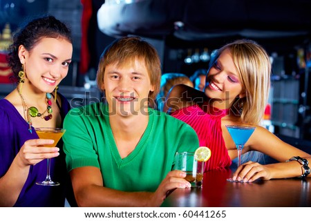Portrait of two girls with martini glasses surrounding happy guy in the nightclub