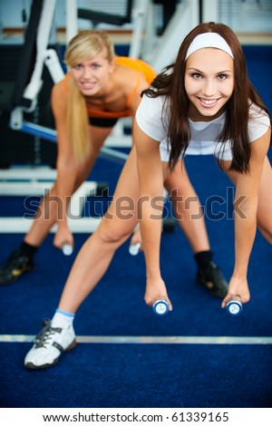 portrait of two girls working out with dumbbells