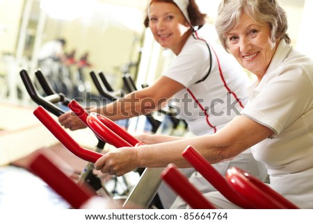Portrait of two good-looking senior women training on exercise machines - stock photo