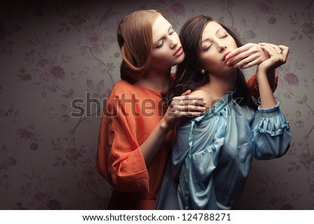 Portrait of two gorgeous girlfriends in blue and orange dresses in a hotel room. Vintage style. Copy-space. Studio shot - stock photo