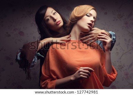 Portrait of two gorgeous girlfriends in blue and orange dresses in a hotel room. Vintage style. Studio shot