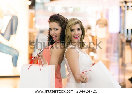 Portrait of two gorgeous women with shopping bags