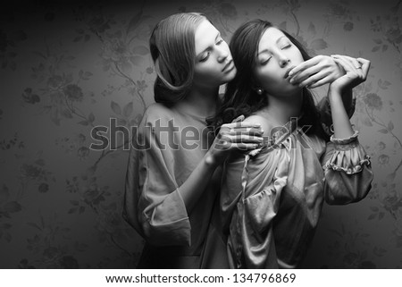 Portrait of two gorgeous young women in vintage dresses in a hotel room. Retro (Hollywood) style. Old classic movie. Film noir. Copy-space. Black and white (monochrome) studio shot - stock photo