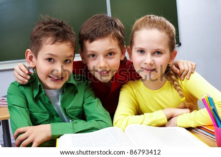 Portrait of two guys and girl sitting in classroom with open book near by