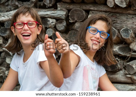 Portrait of two handicapped twin sisters doing thumbs up. - stock photo