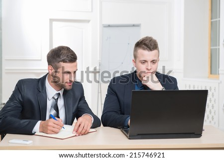 Portrait of Two handsome businessmen in office working on some project, one stressed looking at laptop and another writing in his notebook