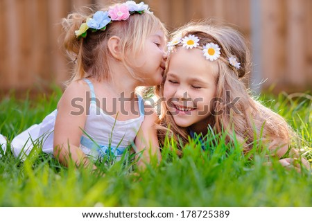 portrait of two happy adorable little  girls sisters on green grass at sunny summer day - stock photo