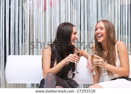 Portrait of two happy attractive girl celebrating with champagne - stock photo