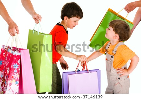 Portrait of two happy boys holding colorful bags between their parents hands - stock photo